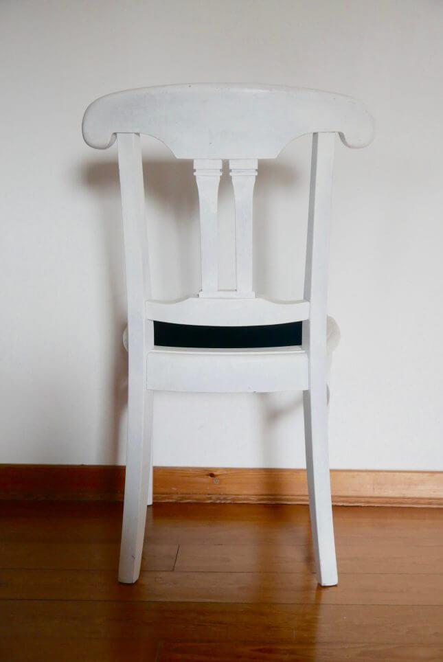 Weißer alter Stuhl mit schwarzem Sitzpolster